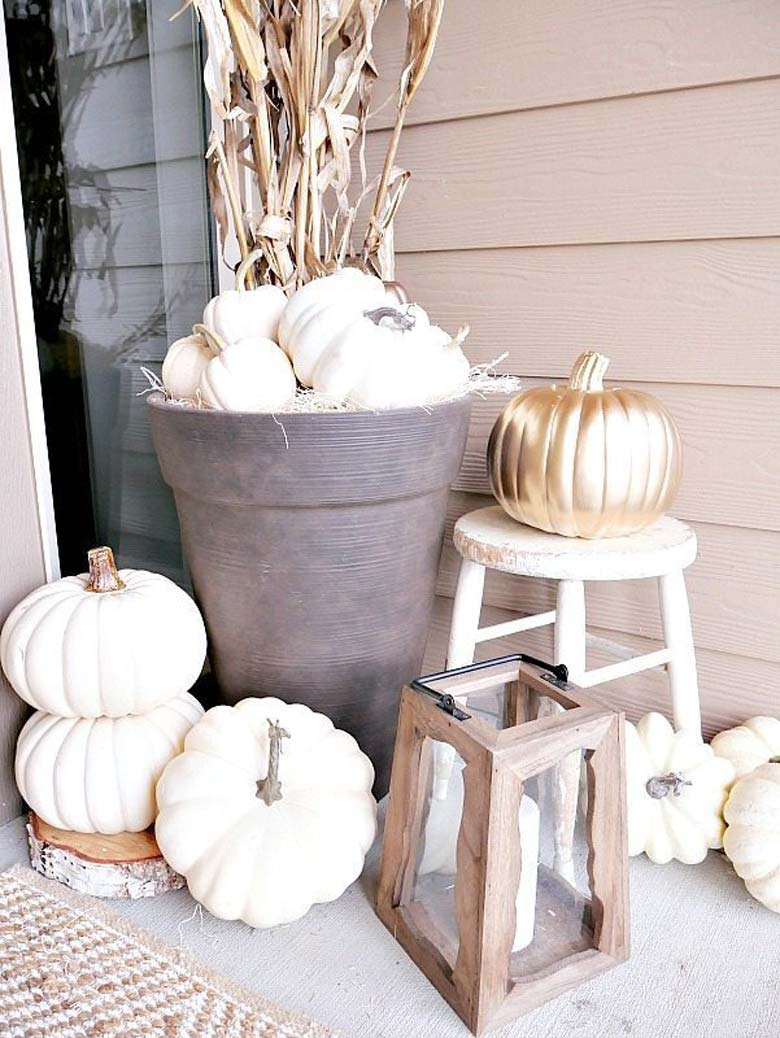small front porch decorating ideas - dark rich neutrals mixed with metallics and a little bit of orangy rust color to decorate for fall; white pumpkins, and bronze paint drip pumpkins with Vibrant mums and cornstalks 'planted' in large dark planters #frontporchideas #outdoorfalldecoratingideas #smallfrontporchdecoratingideas