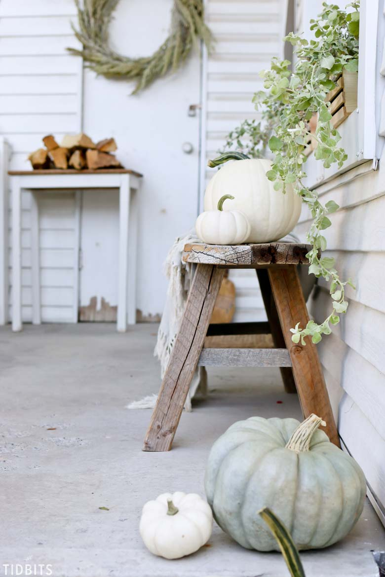 small front porch decorating ideas - old farmhouse charm fall decor with a gorgeous sage wreath, white pumpkin, a light throw, and some greenery #frontporchideas #outdoorfalldecoratingideas #farmhousefalldecor