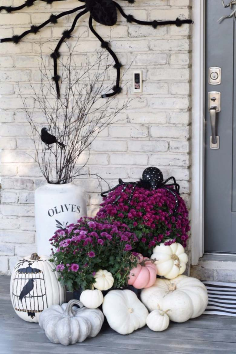 small front porch decorating ideas - pinkFall and Halloween porch decor withwhite and pink pumpkins paired with grey weathered gords, white over-sized vases, simple tree branches, a giant spider, and some black birds silhouettes #frontporchideas #outdoorfalldecoratingideas #smallfrontporchdecoratingideas